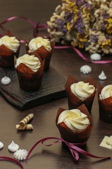 Cupcakes fatti in casa con crema su uno sfondo scuro, concetto per san valentino, compleanno e festa del papà, primo piano