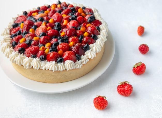 Torta ai frutti di bosco fatta in casa guarnita con panna e bacche di fragole mirtilli e olivello spinoso su una piastra bianca vista in primo piano dall'alto sfondo bianco