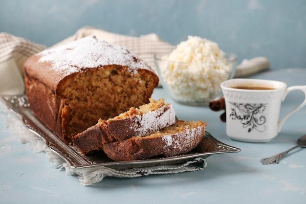 Muffin cagliata fatta in casa su un vassoio di metallo e una tazza di caffè su uno sfondo azzurro, close up