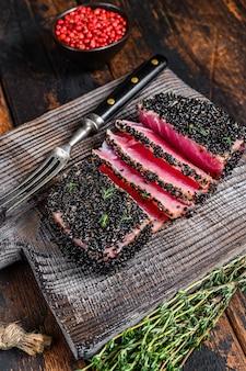 Tagliata fatta in casa bistecca di tonno al sesamo alla griglia su un tagliere. fondo di legno scuro. vista dall'alto.