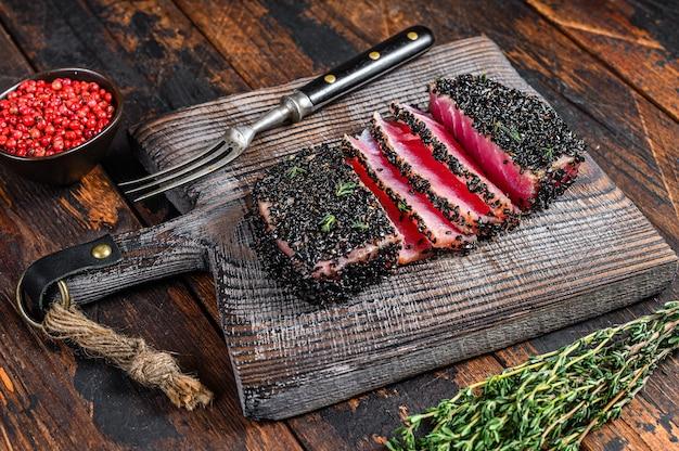 Bistecca di tonno al sesamo alla griglia tagliata in casa su un tagliere