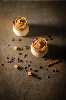 Caffè dalgona fatto in casa su sfondo scuro. accanto a chicchi di caffè e zucchero di canna.