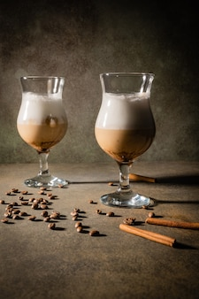 Caffè dalgona fatto in casa su sfondo scuro. accanto a chicchi di caffè e bastoncini di cannella.
