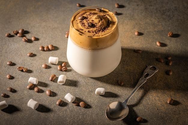 Caffè dalgona fatto in casa su sfondo scuro. accanto a chicchi di caffè e marshmallow.