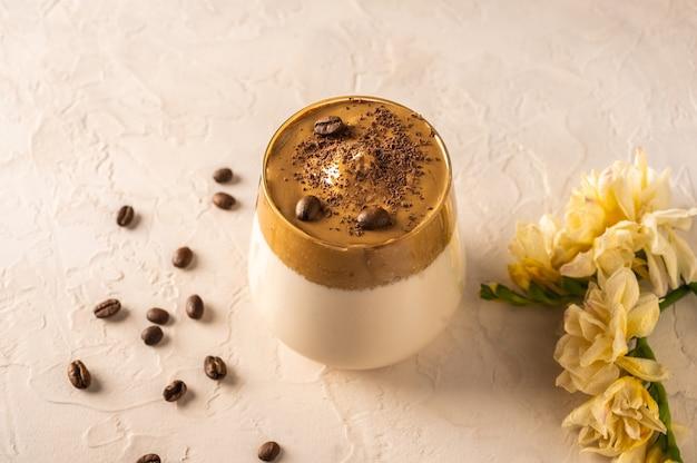 Caffè dalgona fatto in casa su sfondo chiaro. accanto a chicchi di caffè e fiori.