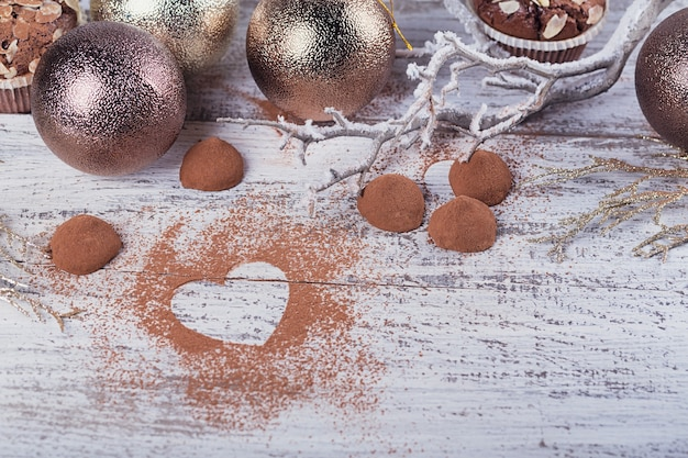 Tartufi di cioccolato fondente fatti in casa con cacao in polvere a forma di cuore e decorazione invernale su tavola in legno rustico bianco. sfondo vacanza invernale. lay piatto con copia spazio per il testo.