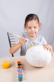 Decorazione fatta in casa per halloween, un bambino dipinge una zucca di carta e tovaglioli, un hobby sull'isolamento.