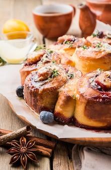 Deliziosi panini alla cannella fatti in casa con limone e frutti di bosco su una superficie di legno