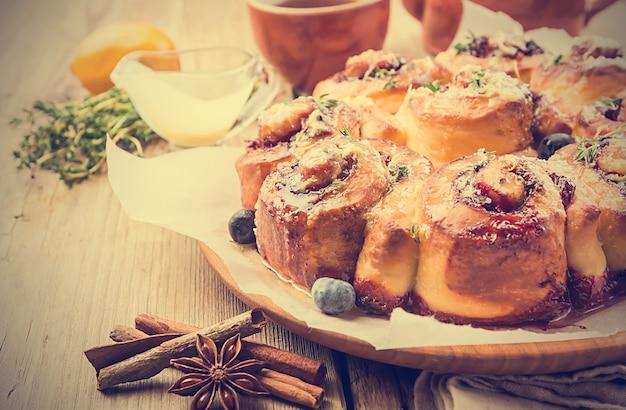 Deliziosi panini alla cannella fatti in casa con limone e frutti di bosco su una superficie di legno Foto Premium