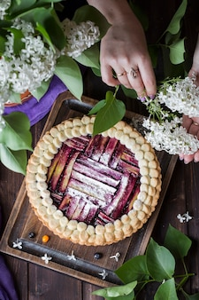 Deliziosa torta di rabarbaro fatta in casa con mirtilli su uno sfondo scuro