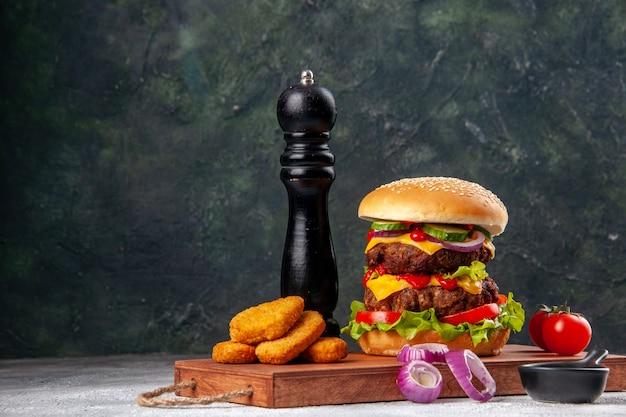 Deliziosi panini fatti in casa e pomodori pepite di pollo cipolle pepe su tagliere di legno ketchup su superficie sfocata