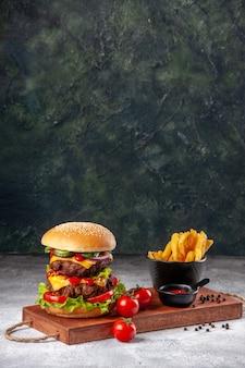Deliziosi panini fatti in casa, pomodori, ketchup, peperoni, patatine fritte su tavola di legno su superficie sfocata