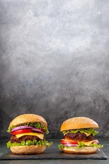 Deliziosi panini fatti in casa su tavola nera su superficie grigia sfocata con spazio libero
