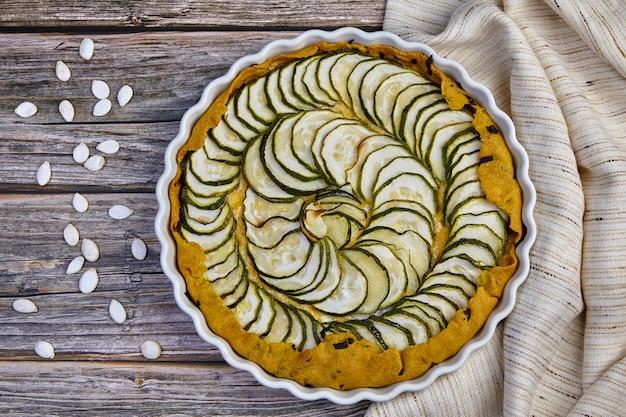 Torta di zucchine, formaggio e basilico deliziosa fatta in casa su un piatto bianco circondato da semi di zucchine