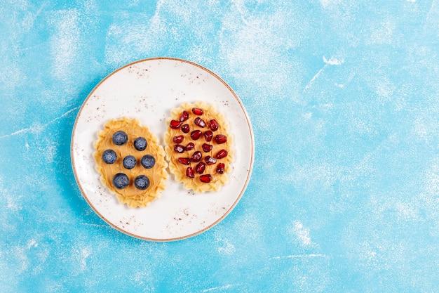 Dolci fatti in casa con mirtilli, fette di kiwi e semi di melograno.