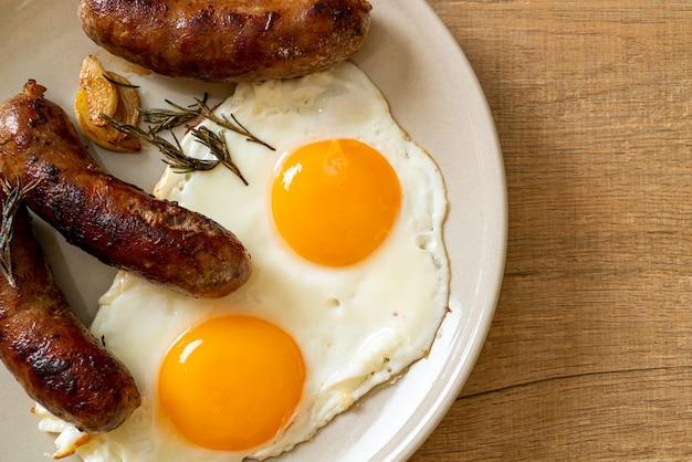 Doppio uovo fritto fatto in casa con salsiccia di maiale fritta - per colazione