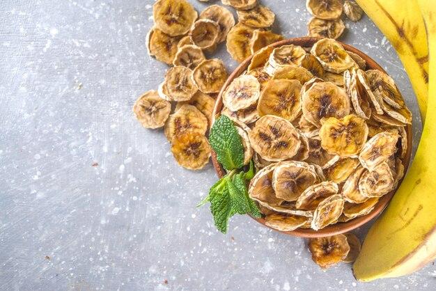 Banane essiccate fatte in casa, chips di banana organica in una ciotola di legno