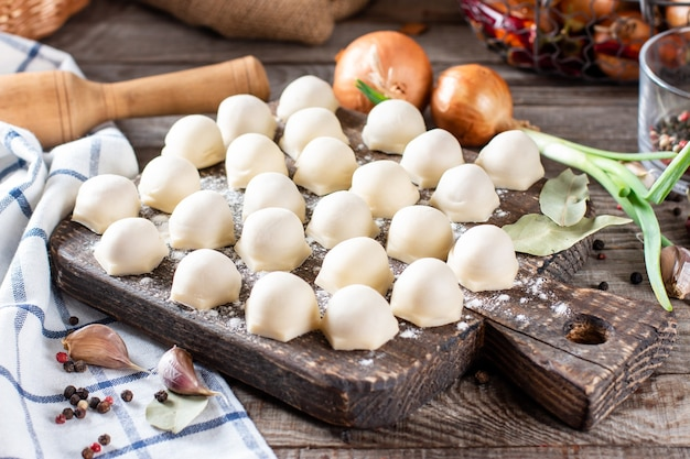 Gnocchi fatti in casa con carne su tavola di legno rustica e tavola con farina, orizzontale