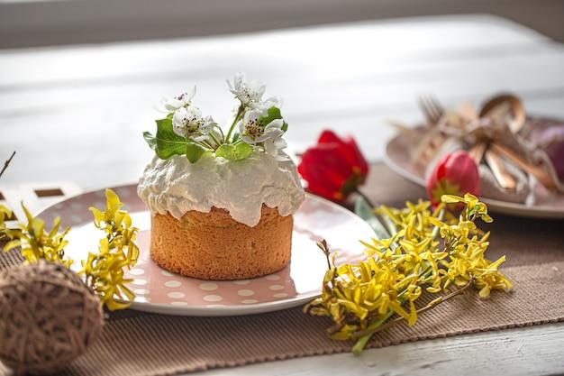 Primo piano di torta di pasqua fatta in casa su un tavolo tra fiori e dettagli di arredamento. concetto di vacanza di pasqua a casa.