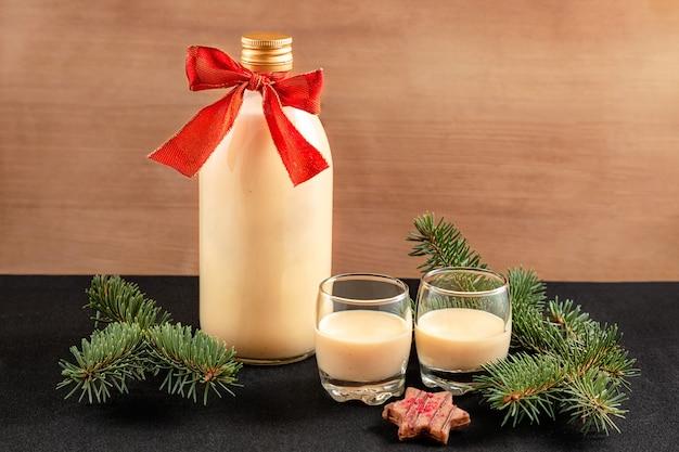 Zabaione fatto in casa in bottiglia e due bicchieri con decorazioni di natale su fondo in legno