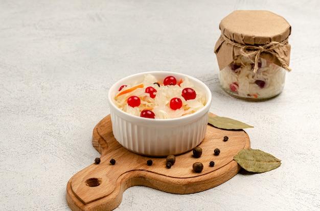 Crauti fermentati fatti in casa con carote e mirtilli rossi in una ciotola bianca su una superficie grigio chiaro