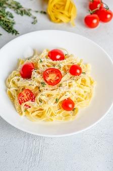 Fettuccine fatte in casa con pomodori, timo, parmigiano in un piatto bianco su una superficie leggera