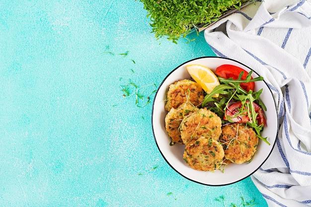 Crocchette di pesce fatte in casa con pesce bianco, bulgur, spinaci e pangrattato. frittelle di baccalà tritato. pranzo o cena deliziosi e nutrienti. vista dall'alto, dall'alto