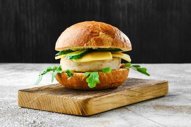Fishburger fatto in casa con formaggio, rucola e cetriolo sul tagliere di legno