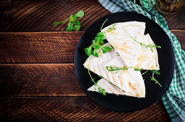 Focaccia fatta in casa con prosciutto, formaggio e pomodori ed erbe verdi