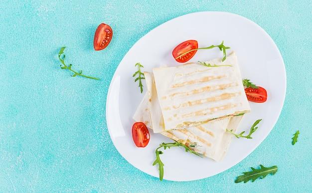 Focaccia fatta in casa con prosciutto, uova, formaggio e pomodori ed erbe verdi