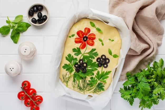 Focaccia ai fiori fatta in casa. focaccia cruda decorata in modo creativo con verdure su carta forno. pasta a lievitazione naturale. pane italiano decorato. vista dall'alto.