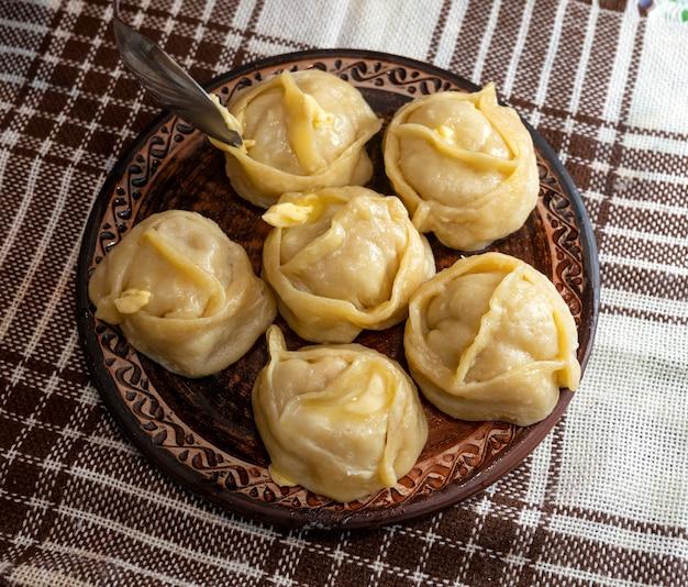 Concetto di cibo fatto in casa. manti caldi fatti in casa pronti sul piatto