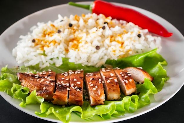 Cibo fatto in casa - pollo teriyaki con riso bianco e pepe su sfondo nero.