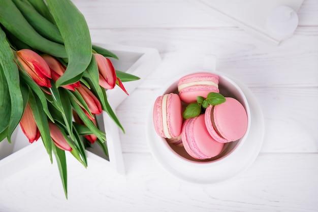 Macarons rosa dolci fatti in casa francesi e tulipani rossi primaverili