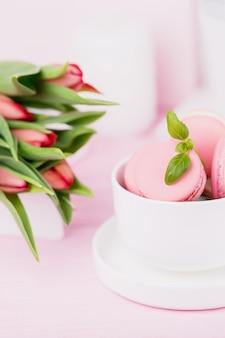 Macarons rosa dolci fatti in casa francesi e tulipani primaverili