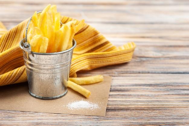 Patatine fritte fatte in casa in un piccolo secchio di latta con un pizzico di sale sulla tavola di legno con tovagliolo giallo