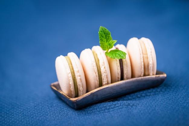 Amaretti francesi fatti in casa alla vaniglia con foglia di menta su un classico blu