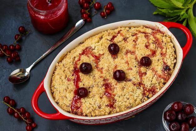 Torta sbriciolata di ciliegie fresca fatta in casa con farina integrale in forma ceramica su sfondo scuro, pronta da mangiare, primo piano, foto orizzontale