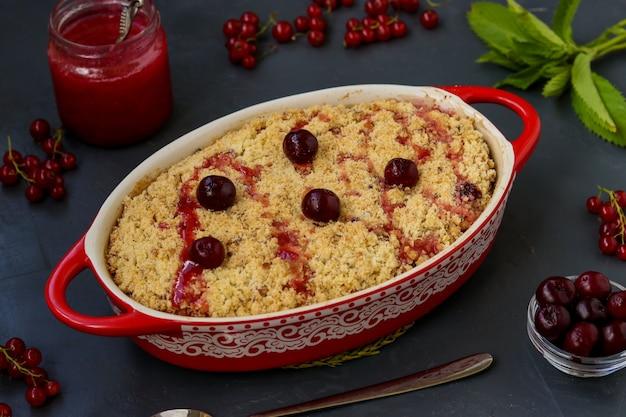 Torta fresca casalinga della briciola della ciliegia con farina integrale nella forma ceramica su un fondo scuro, foto pronta da mangiare e orizzontale