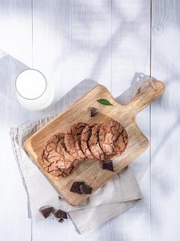 Biscotti al cioccolato freschi fatti in casa con gocce di cioccolato sul tagliere e bicchiere di latte su un tavolo in legno di mattina leggera. vista dall'alto e copia spazio