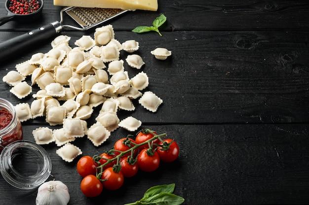 Pasta italiana fresca fatta in casa dei ravioli sulla tavola di legno nera