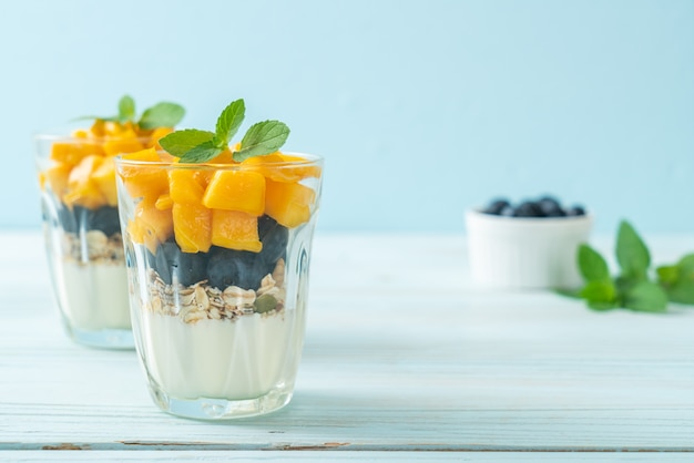 Mango fresco fatto in casa e mirtillo fresco con yogurt e muesli - stile di cibo sano