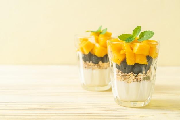 Mango fresco fatto in casa e mirtilli freschi con yogurt e muesli