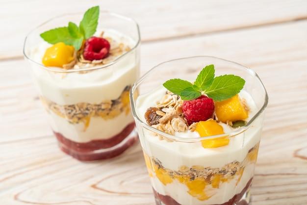 Mango fresco fatto in casa e lampone fresco con yogurt e muesli - stile di cibo sano