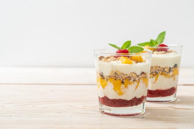 Mango fresco fatto in casa e lampone fresco con yogurt e muesli - stile di cibo sano Foto Premium