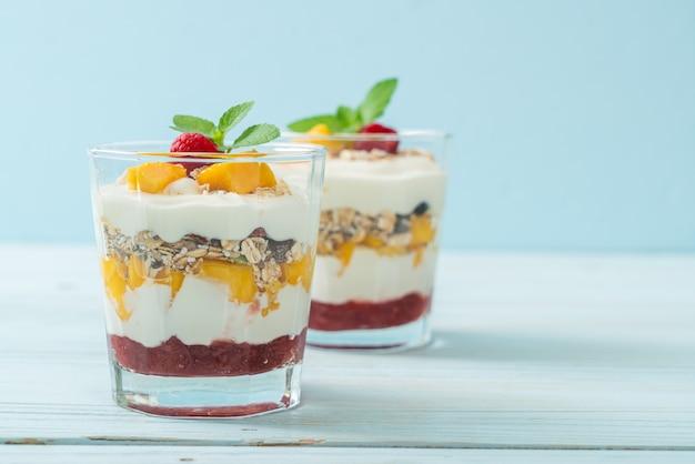 Mango fresco fatto in casa e lamponi freschi con yogurt e muesli. stile di cibo sano