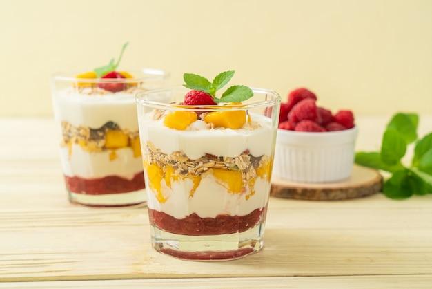 Mango fresco fatto in casa e lampone fresco con yogurt e muesli - stile alimentare sano healthy