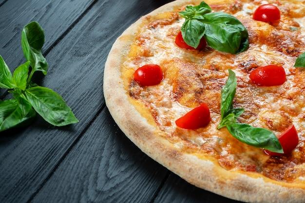 Pizza fresca fatta in casa margherita con salsa rossa, basilico e pomodoro ciliegia su un legno nero con spazio di copia.