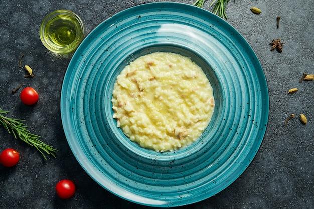 Risotto fatto in casa e fresco con pancetta e pollo. riso tradizionale italiano in un piatto di ceramica rosa su una superficie nera in una composizione con ingredienti