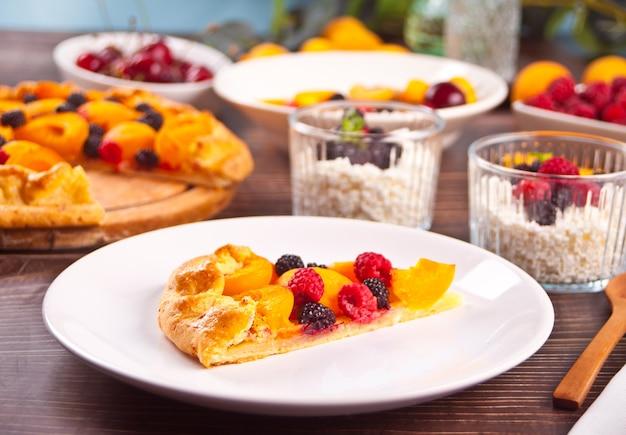 Crostata di albicocche appena sfornate fatta in casa con frutta fresca e bacche sul piatto bianco.